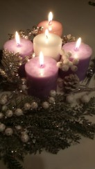five lit candles, three purple, one pink, one white