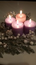 four lit candles. three purple, one pink