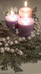 lit candles, two purple one pink, silver wreath