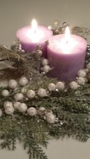 two lit purple pillar candles with silver decor around them