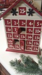 advent calendar shaped like house, with 24 little doors to open, shows two doors open